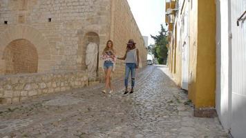 Zwei Freundinnen gehen mit einem Reiseführer durch das alte Ibiza video