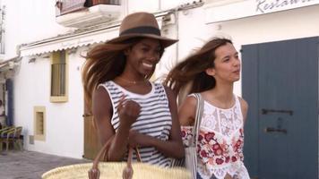 zwei freundinnen, die in den straßen von ibiza spazieren gehen, spanien, erschossen auf r3d video