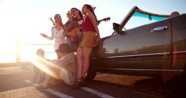 Amigos adolescentes hipster celebrando un atardecer en la playa con una guitarra