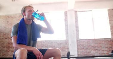 junger erwachsener Kerl, der im Fitnessstudio während des Fitnesstrainings hydratisiert