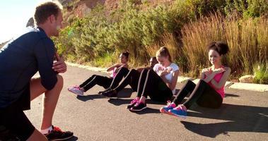 Gruppe junger erwachsener Athleten, die draußen Sit-ups machen