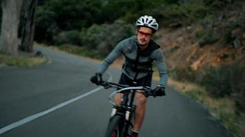 giovane ciclista adulto in sella alla sua bicicletta su una strada di montagna video