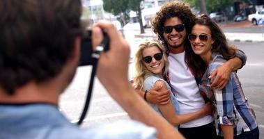 jeune homme photographiant ses amis avec un appareil photo