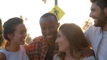 Grupo de amigos adultos jóvenes sonrientes abrazándose en la calle