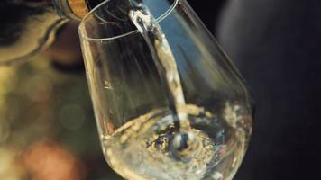 junger erwachsener Junge gießt Weißwein in ein Glas. Nahaufnahme.