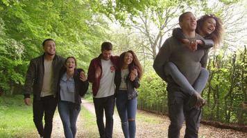 Young adults walking and piggybacking in a country lane, shot on R3D