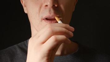Gesicht eines jungen erwachsenen Mannes, der ein paar Zigaretten in den Mund nimmt video