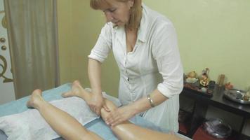 la massaggiatrice adulta fa un massaggio curativo dei piedi sinistri alla giovane donna nel salone