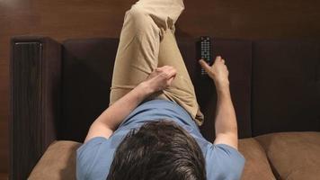Draufsicht: junger erwachsener Mann wechselt zu Hause einen Fernsehkanal per Fernbedienung auf einem Sofa video