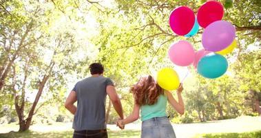 Paar läuft mit bunten Luftballons in einem sonnigen Park