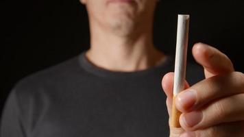 jovem adulto segura um cigarro com uma das mãos e depois o quebra video