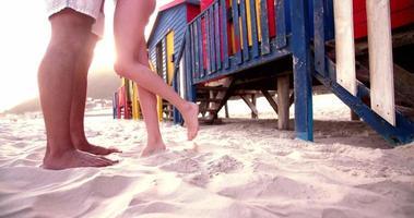 les jambes du couple face à face dans le sable sur la plage