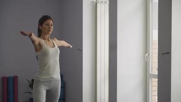 donna che fa la posa di yoga del guerriero