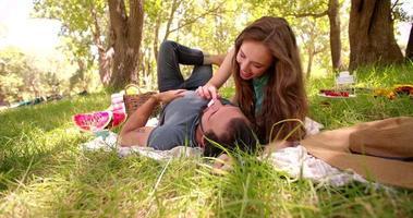 ragazza scherzosamente alimentando il suo ragazzo al cioccolato in un parco