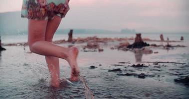 ragazza in abito floreale boho che attraversa un lago naturale