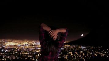 jovem levantando os braços com as luzes da cidade além