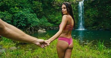 mulher levando o homem para a cachoeira