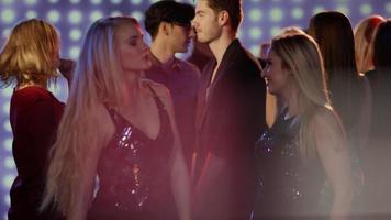 Zwei blonde Mädchen tanzen in der Menge im Club