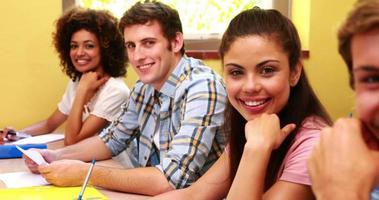 alunos sentados em uma fila sorrindo para a câmera