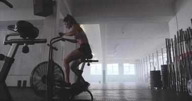 giovane donna adatta utilizzando cyclette in palestra video