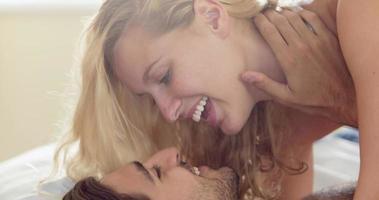 linda pareja joven acostada en la cama y besándose