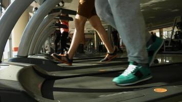 hommes qui courent sur un tapis roulant dans une salle de sport.
