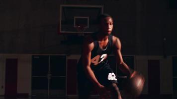 Nahaufnahme eines Basketballspielers auf dem Platz, der in Richtung Kamera tröpfelt, dunkles Licht