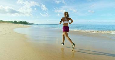junge Frau läuft am Strand