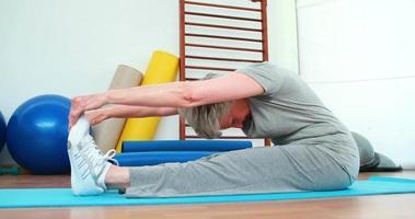 donna anziana toccando le dita dei piedi sulla stuoia di esercizio