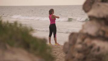 giovane donna attiva facendo fitness che si estende sulla spiaggia