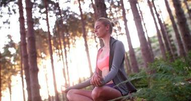 Frau in Sportkleidung, die Yoga-Pose im Morgenwald durchführt