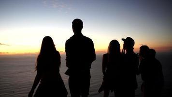adolescenti guardando l'oceano dopo il tramonto su una montagna video