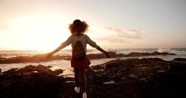 Adolescente afro hipster girando algunas rocas en la playa al atardecer