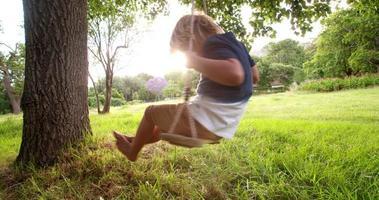ragazzo allegro che gioca sull'altalena nel parco al tramonto