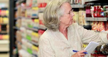 ältere Frau, die im Lebensmittelgeschäft einkauft