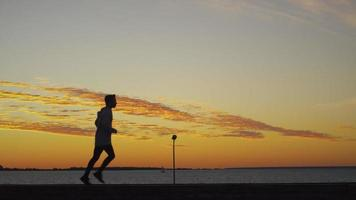 Mann, der entlang der Küste zur Sonnenuntergangszeit joggt