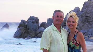 Ein älteres Ehepaar lächelt und küsst am Strand