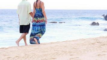 ein älteres Ehepaar, das sich an den Händen hält und vor großen Felsen den Strand entlang geht