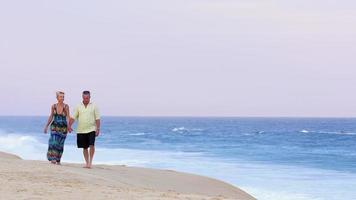 ein älteres Ehepaar, das sich an den Händen hält und den Strand entlang geht