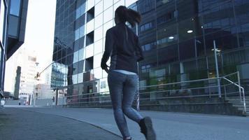 donna che corre verso l'esterno fotocamera in ambiente urbano video
