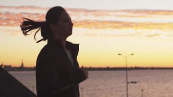 mulher correndo ao longo da costa ao pôr do sol