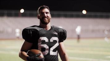 Portrait of a football player on the field at night video
