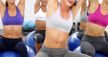 Fitnessklasse sitzen auf Übungsbällen, die sich dehnen video