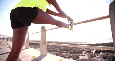 Corredor afroamericano haciendo ejercicio en la playa video