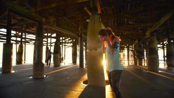 Frau, die am Strand bei Sonnenuntergang ausarbeitet. Fitness aktiver Lebensstil. Laufen auf dem Sand