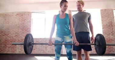Mädchen, das mit Gewichten trainiert, die von ihrem persönlichen Trainer geleitet werden video