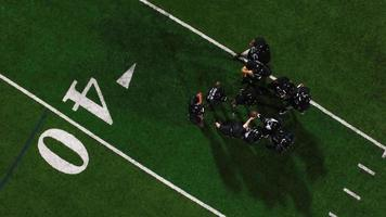 The camera spins from above as a football team in a huddle gets hyped and runs onto the field