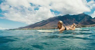 bella ragazza pagaiando con la tavola da surf sull'onda blu dell'oceano