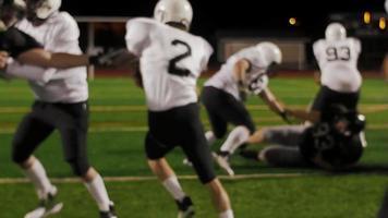 un giocatore di football gli viene consegnato la palla e fa un touchdown