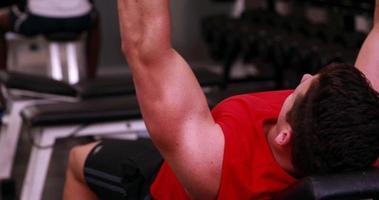 Colocar hombre levantando pesas tumbado en el banco video